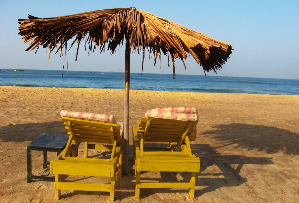 Two chairs under a thatch umbrella on a beach