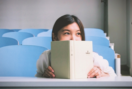 Girl with a book. Photo by Poodar Chu, Unsplash.