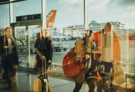 Travellers walking through an airport with suitcases. Photo by Negative Space, Pexels.