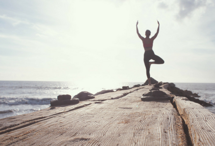 Person doing yoga on a wooden walkway. Photo by Marion Michele, Unsplash.