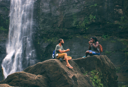 Two people sitting on a rock next to a waterfall. Photo by Nandhu Kumar, Pexels.
