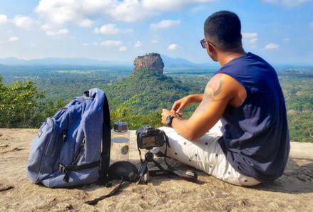 Man sitting on a mountaintop with a backpack.